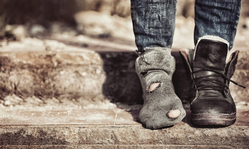Image of feet, one foot with a shoe, the other foot with just a sock on