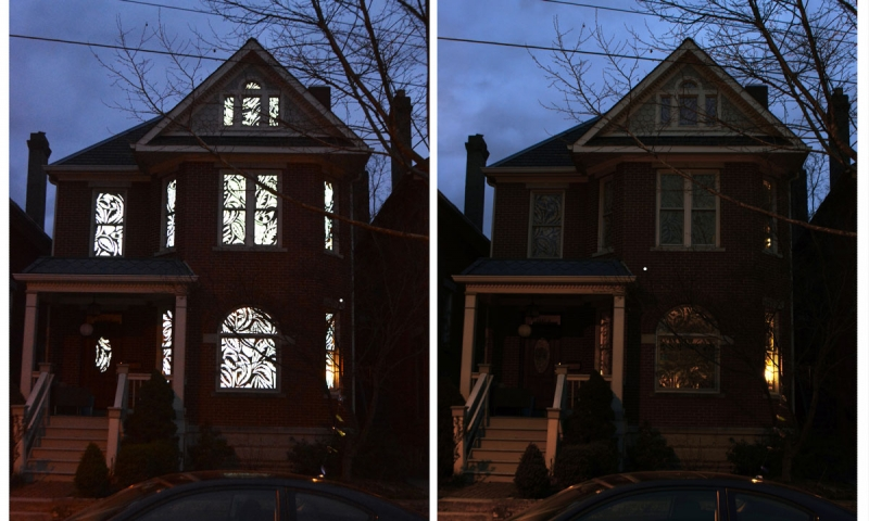 Exterior of house with all lights on next to house with lights off