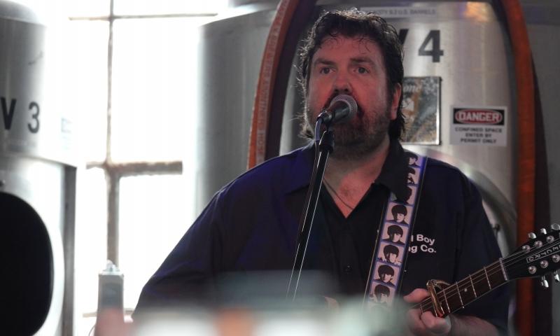Image of man singing and playing guitar